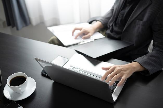 Empresário de tiro recortado analisando algum documento e trabalhando com o laptop.