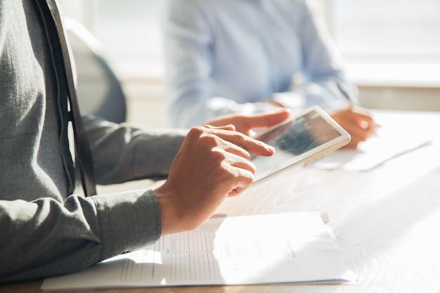 Empresário de trabalho com a tabuleta digital no escritório