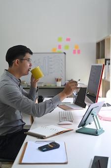 Empresário de vista lateral bebendo café e trabalhando com o computador.