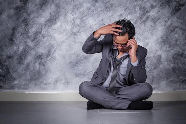 Empresário deprimido com telefone móvel e sentado no chão