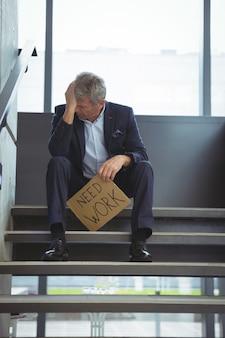 Empresário deprimido sentado na escada segurando uma folha de papelão com texto precisa de reparos