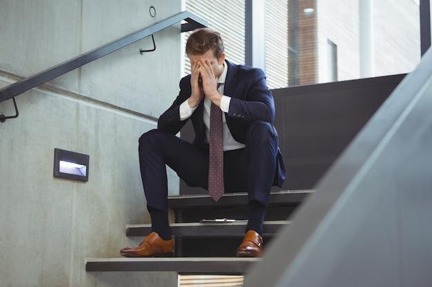 Empresário deprimido sentado na escada