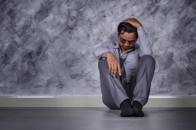 Empresário deprimido sentado no chão