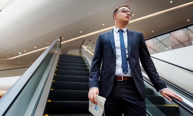 Empresário descendo uma escada rolante
