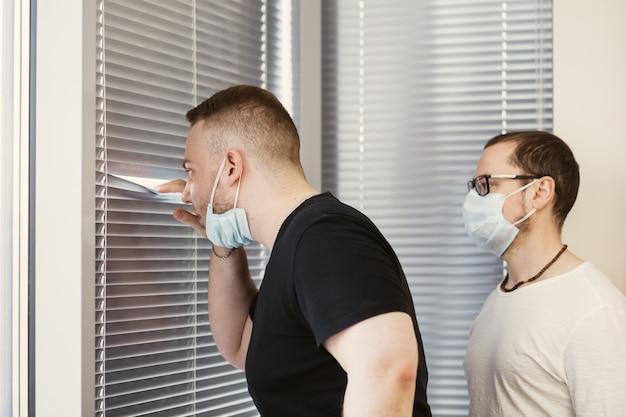 Empresário descolados, espreitar através das cortinas no escritório