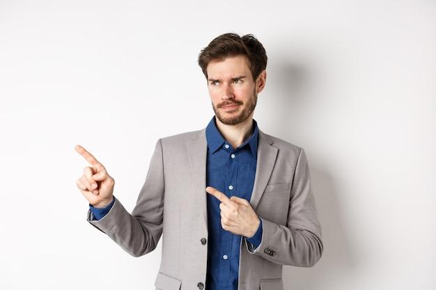 Empresário descontente em terno apontando e olhando para a esquerda com um sorriso cético, bandeira de antipatia, oferta promocional de desaprovação, de pé sobre fundo branco.