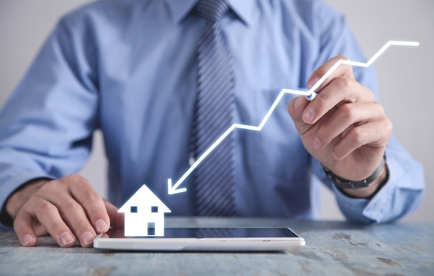 Empresário desenhando a seta para baixo e a casa. queda do mercado de preços imobiliários