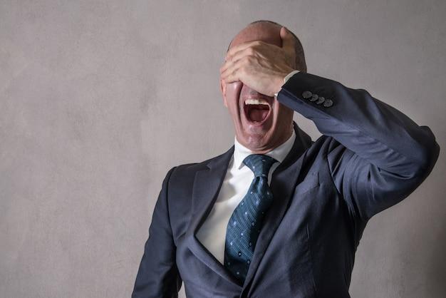 Empresário desesperado com a mão na cara