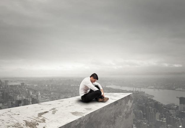 Empresário desesperado sozinho se senta em um telhado. conceito de solidão e fracasso