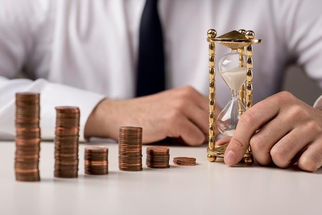 Empresário desfocado com moedas e ampulheta