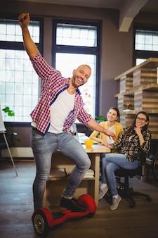 Empresário, desfrutando de placa auto-equilibrada no escritório criativo