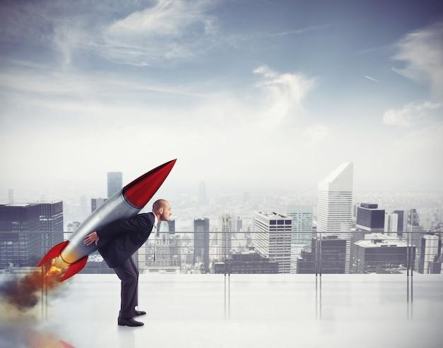 Empresário determinado voando com um foguete do telhado de um arranha-céu