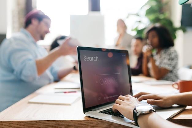 Empresário digitando em um laptop em uma sala de reuniões