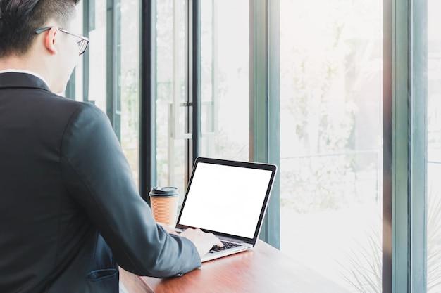 Empresário digitando no laptop com uma xícara de café no escritório doméstico ou no café