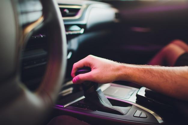 Empresário, dirigindo o carro moderno de luxo na cidade. feche a mão do homem na caixa de velocidades.