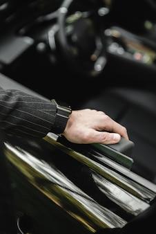 Empresário, dirigindo um carro esportivo de luxo. mão na alça. close de um homem em traje formal abrindo a porta do carro