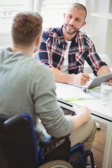 Empresário discutindo com colega de handicap no escritório