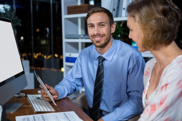 Empresário discutindo com o colega sobre tablet digital