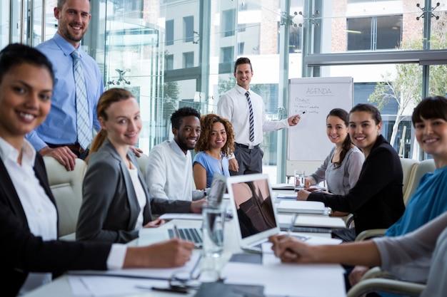 Empresário discutindo no quadro branco com colegas de trabalho