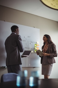 Empresário discutindo no quadro branco com um colega