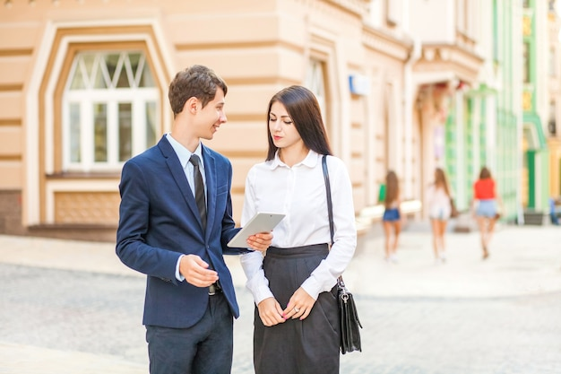 Empresário distraído e olhando para garotas sensuais enquanto trabalha e discute com o parceiro