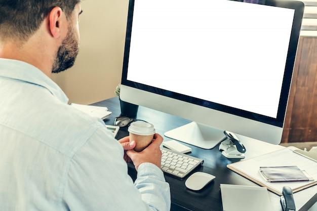Empresário do jovem sentado à sua mesa de trabalho no escritório