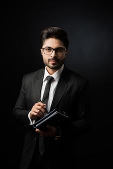 Empresário do sexo masculino indiano escrevendo em um diário em pé contra um fundo preto, iluminação sombria, foco seletivo