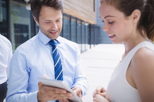 Empresário e colega discutindo sobre tablet digital