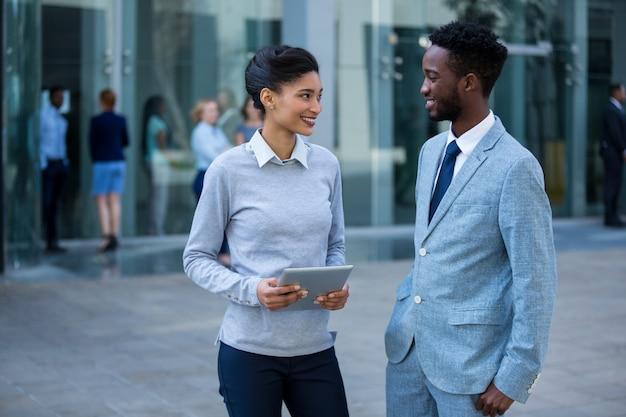Empresário e colega interagindo no prédio de escritórios