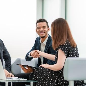 Empresário e empresária apertando as mãos após discutir o contrato. conceito de cooperação