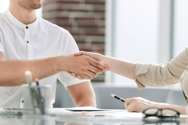 Empresário e empresária apertando as mãos enquanto estão sentados na mesa
