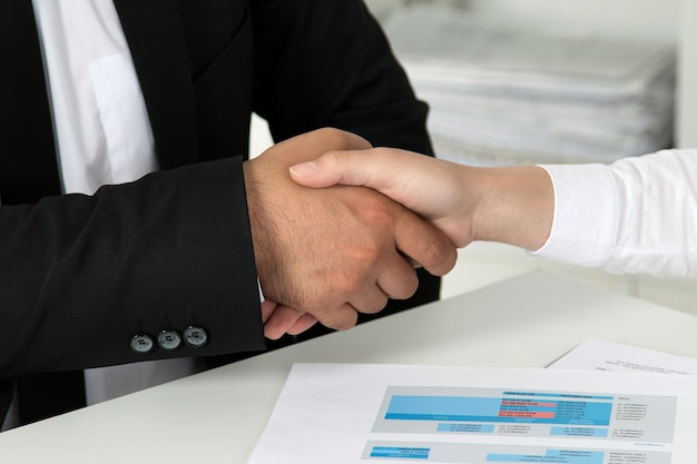 Empresário e empresária apertando as mãos, terminando uma reunião. vista de perto.