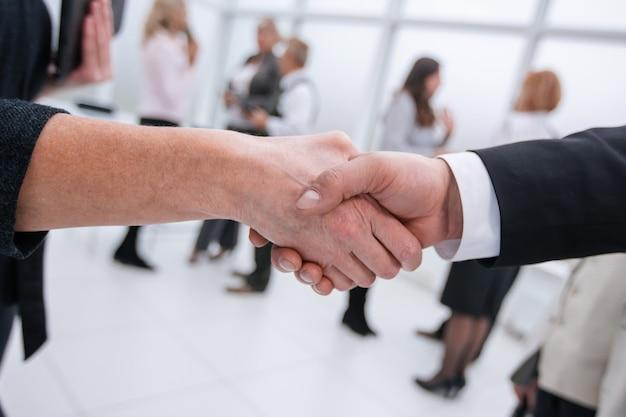 Empresário e empresária apertando as mãos