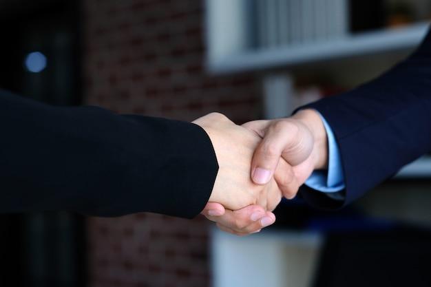Empresário e empresária aperto de mão na reunião corporativa de parceria