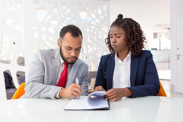 Empresário e empresária assinando contrato