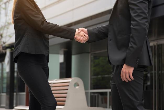 Empresário e empresária estão apertando as mãos na frente do prédio de escritórios