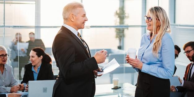 Empresário e empresária falando em pé no escritório.