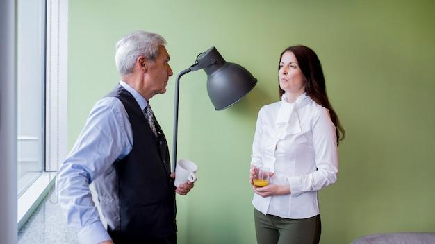 Empresário e empresária interagindo durante uma pausa no escritório