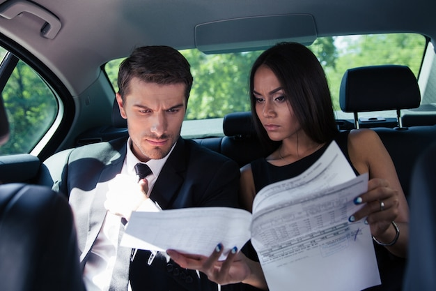 Empresário e empresária lendo documentos no carro