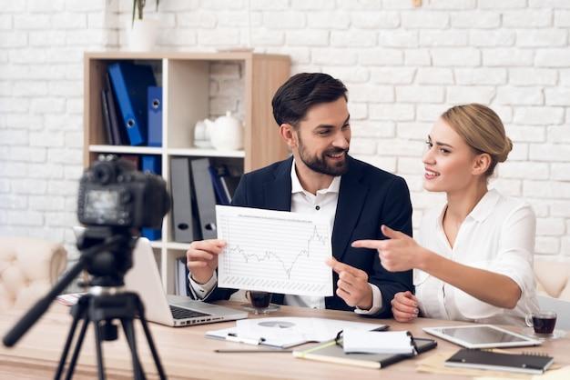 Empresário e empresária mostrando gráficos.
