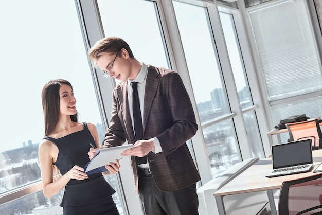 Empresário e empresária no escritório trabalhando juntos em pé perto da janela mulher segurando um acordo olhando para homem sorrindo alegre sinalizando