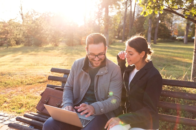 Empresário e empresária usando laptop enquanto está sentado no banco do parque