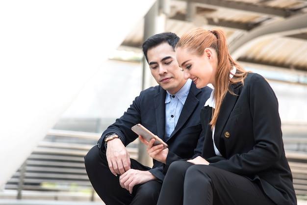Empresário e empresárias lendo mensagem no telefone inteligente
