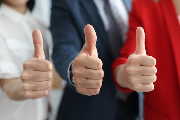Empresário e empresárias mostrando gesto de ok com o polegar para cima