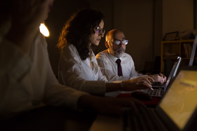 Empresário e empresárias trabalhando com laptops