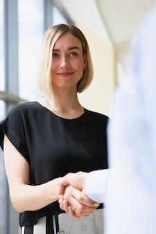 Empresário e mulher apertam as mãos como olá
