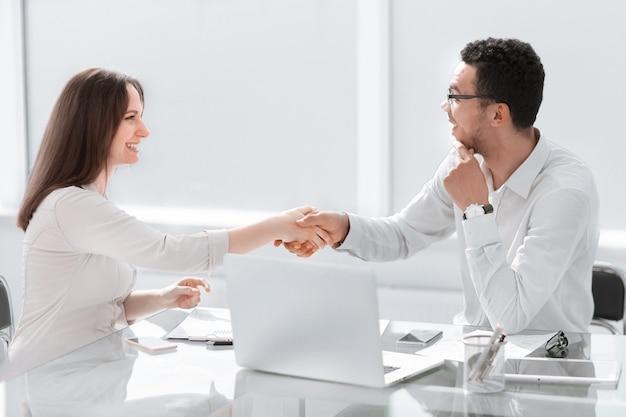 Empresário e mulher de negócios apertando as mãos no escritório