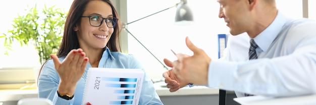 Empresário e mulher de negócios estão sentados à mesa no escritório, tendo o diálogo.