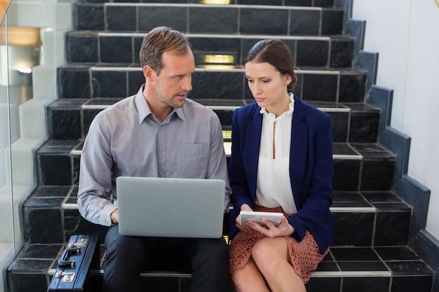 Empresário e mulher sentada nos degraus usando laptop