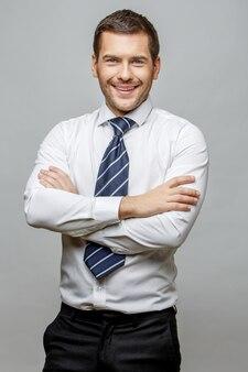 Empresário elegante bonito sobre fundo cinza